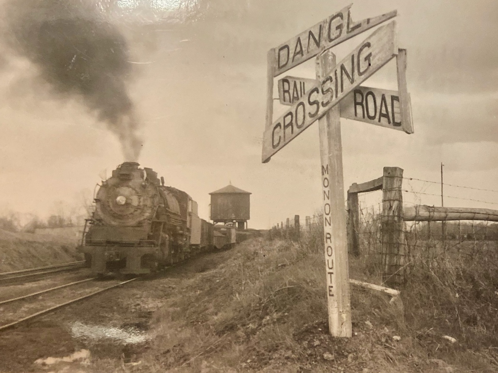 A sepia image of an old train at a railroad crossing